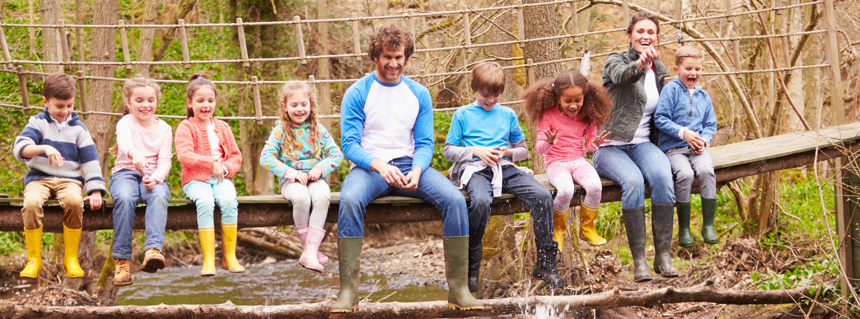 Adults With Children On Bridge At Outdoor Activity Centre